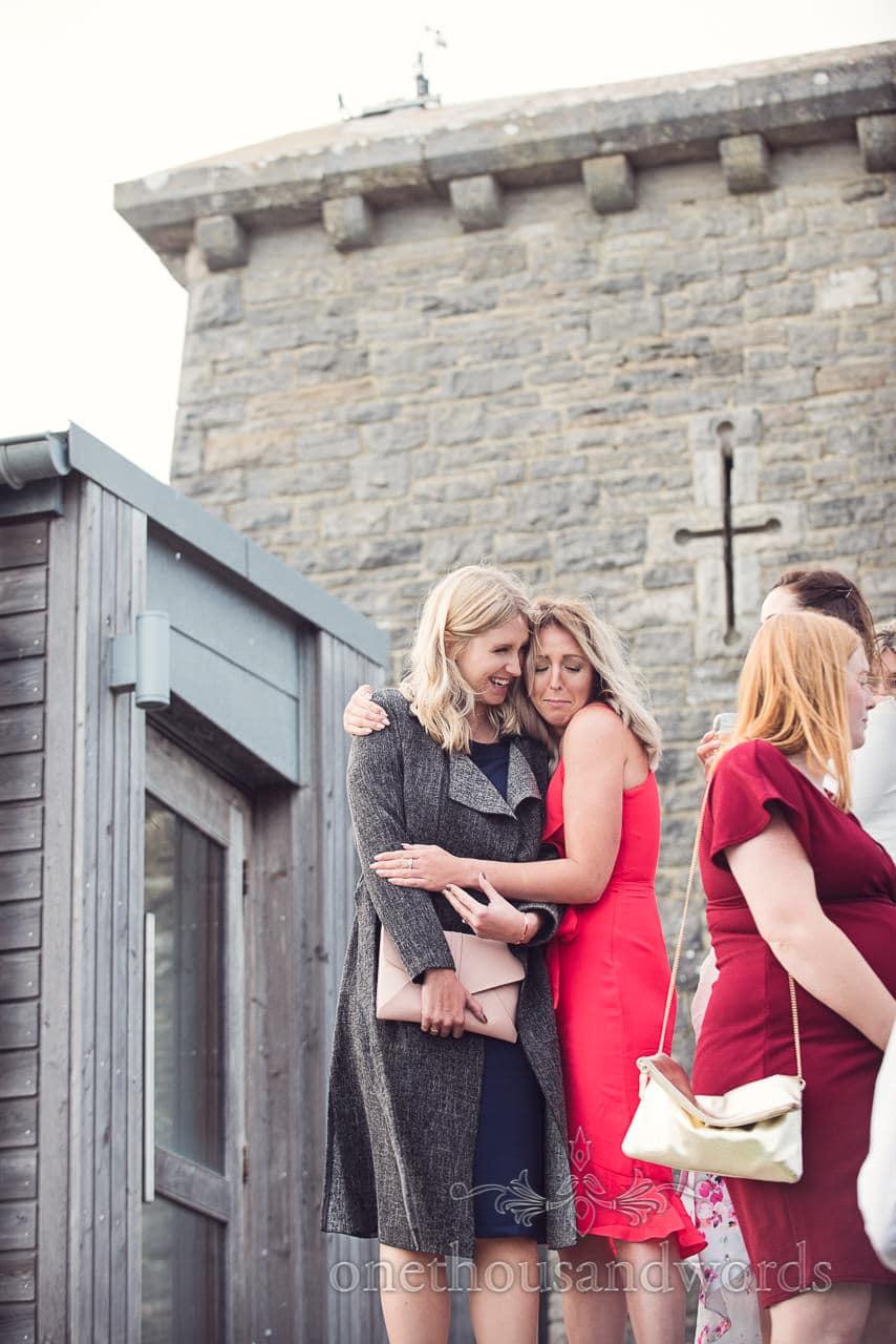 Wedding guests hugging outside Durlston Castle Wedding reception in Dorset
