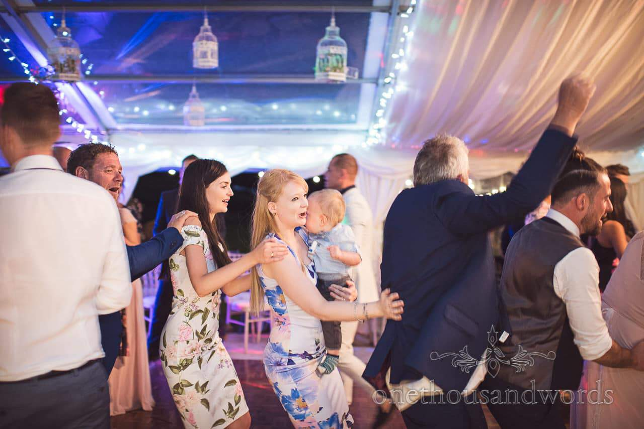 Wedding guests in floral print dresses in the conga line at Purbeck Valley Farm wedding