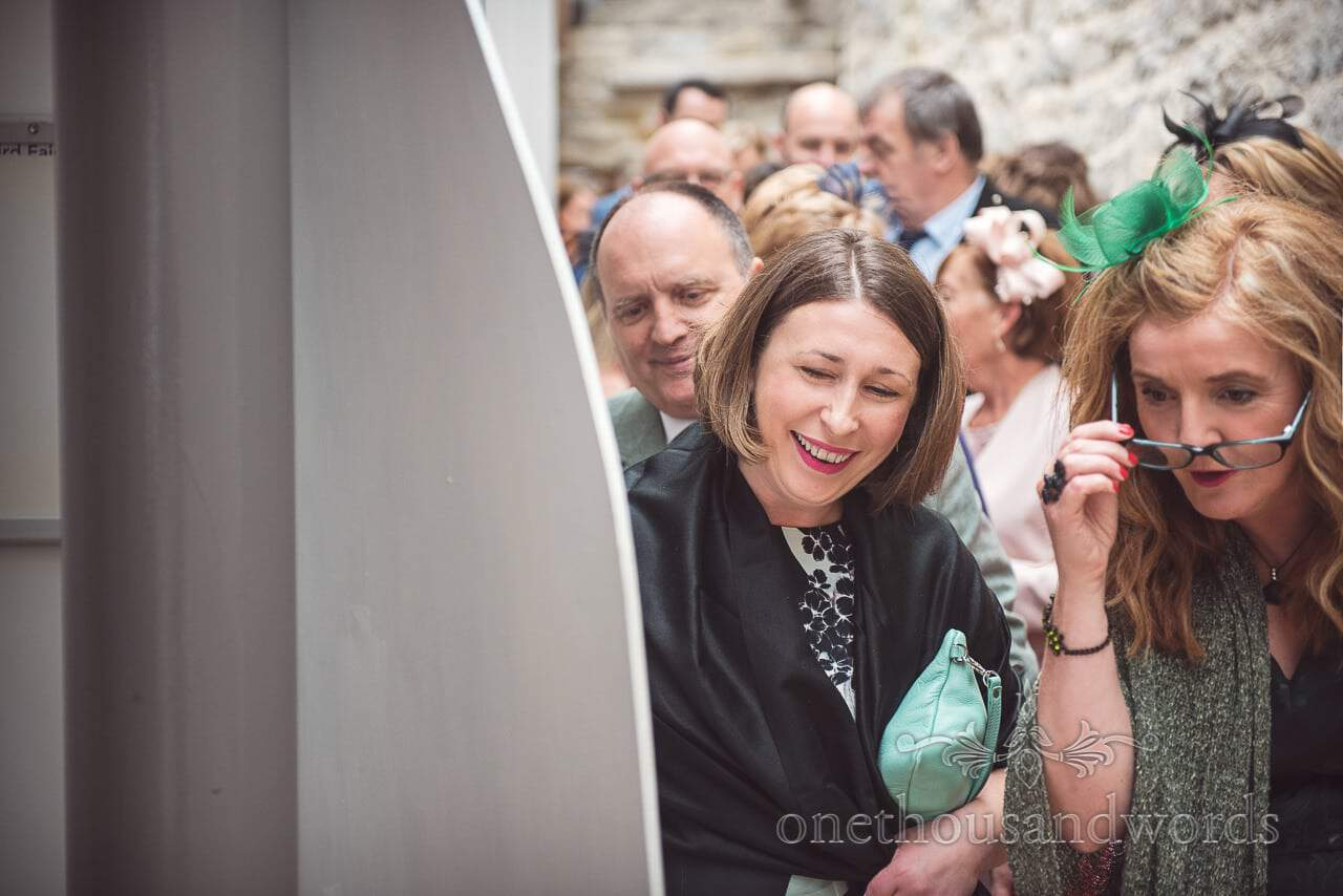 Wedding guests look at table plan at Durlston Castle Wedding Photographs