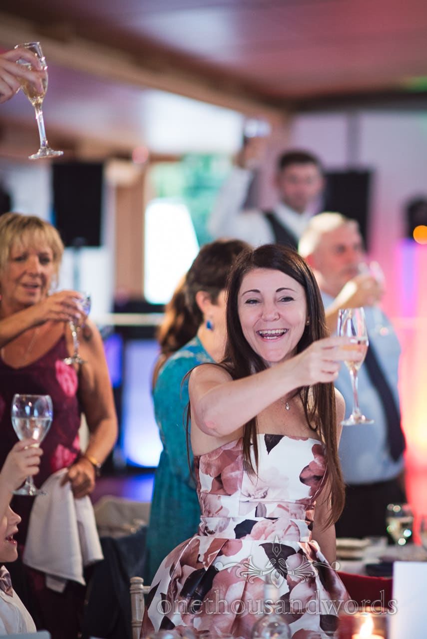 Wedding guests raise champagne glasses during Durlston Castle Wedding Speeches