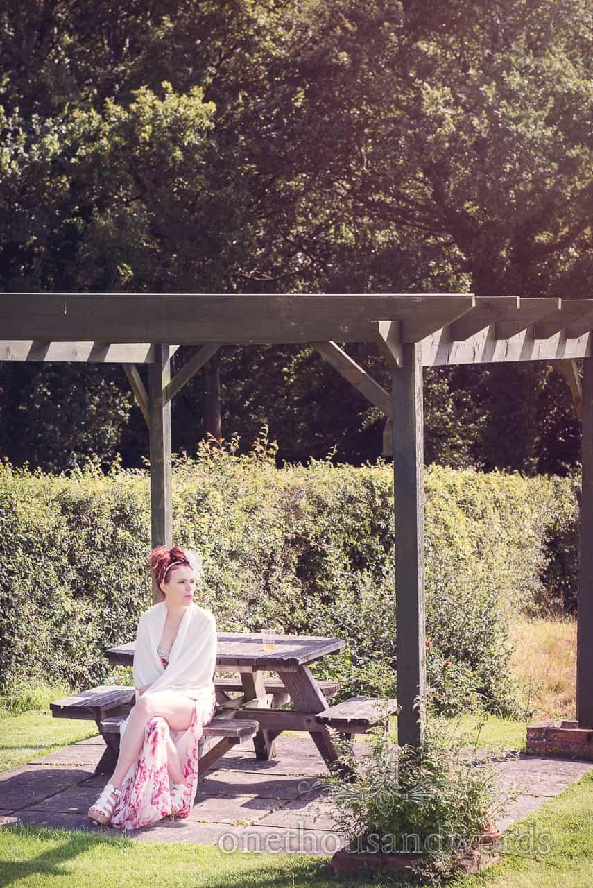 Wedding guests takes a break in garden at Coppleridge Inn Wedding Photographs