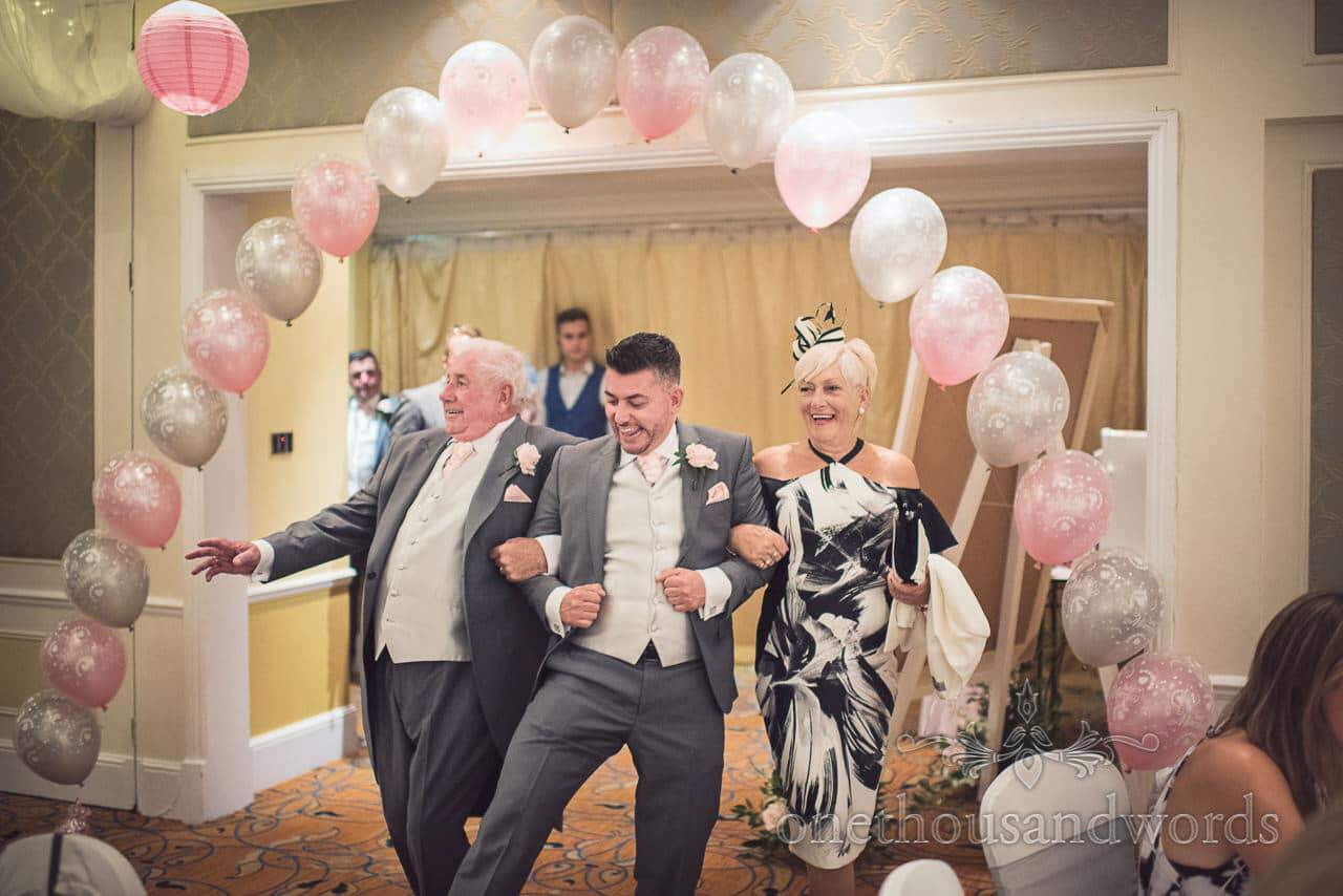 Wedding guests walk under pink and grey balloon archway at Bournemouth Hotel wedding