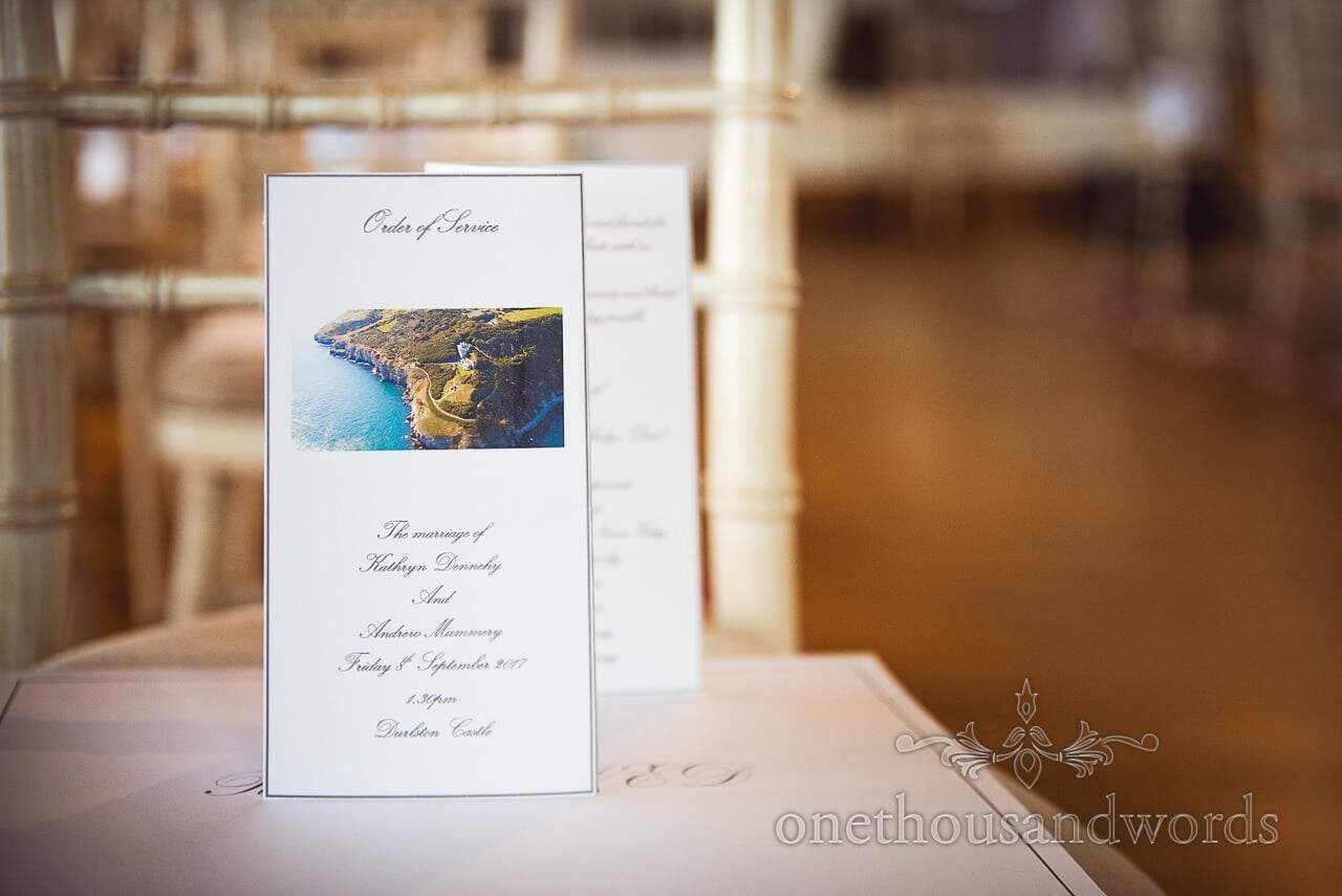 Wedding order of service with aerial photograph on chair at Durlston Castle Wedding venue