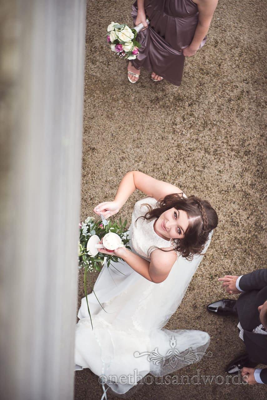 Wedding photograph looking down at bride eating ice cream at Durlston Castle