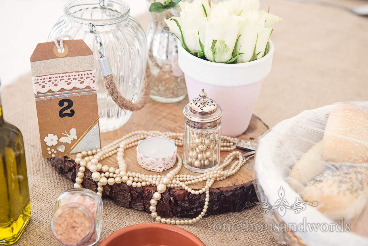 Wedding table center details on wooden tree slice with pearls, beads flowers and jars