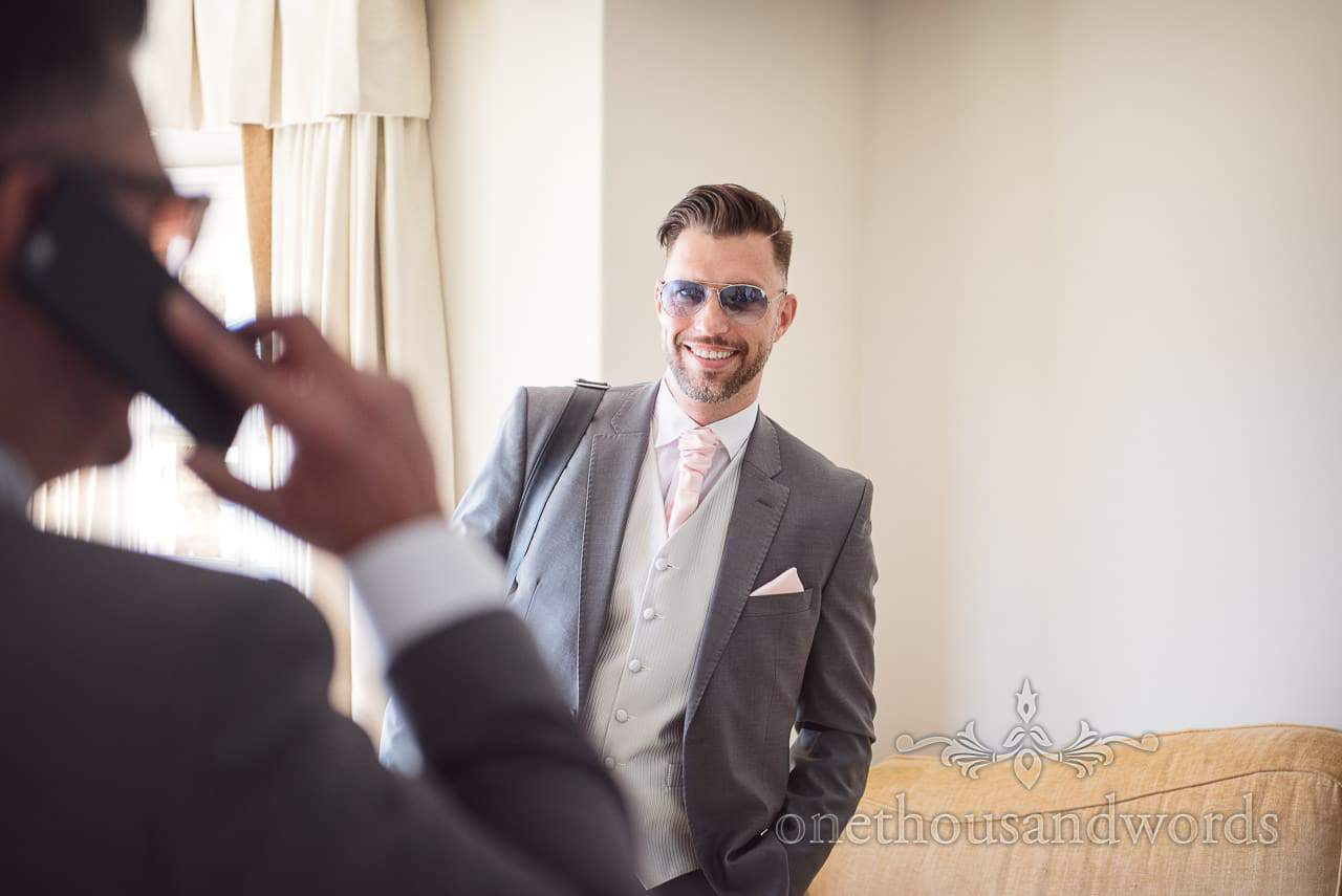 Well groomed groomsman in grey suit with pink tie and handkerchief with sunglasses