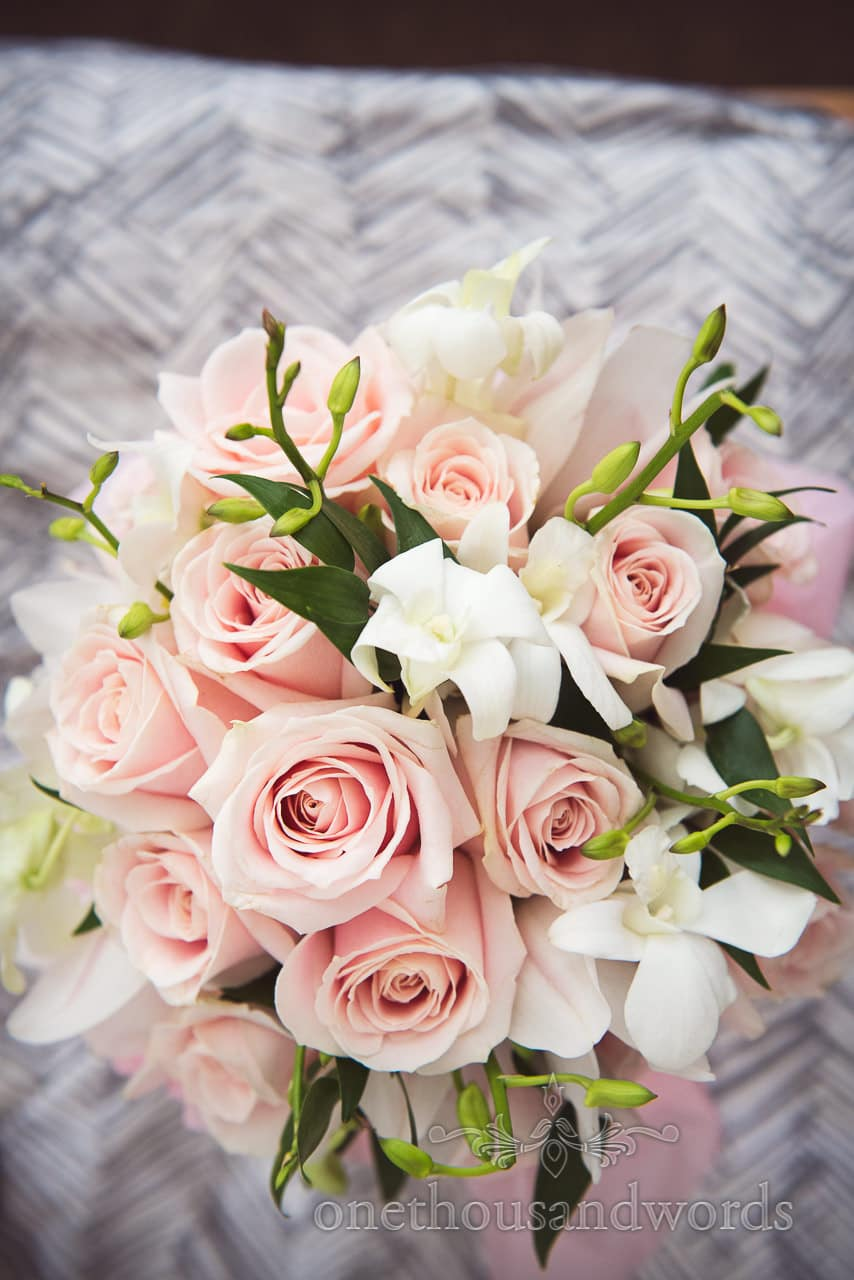 White and pink wedding bridal bouquet with green foliage and pink roses
