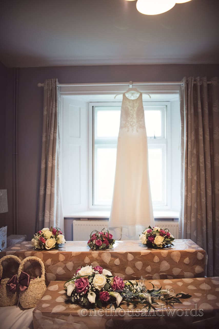 White and purple wedding flower bouquets with wedding dress hanging in background