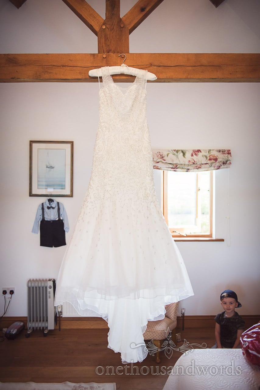 White detailed trumpet wedding dress hangs in front of pageboy wedding outfit