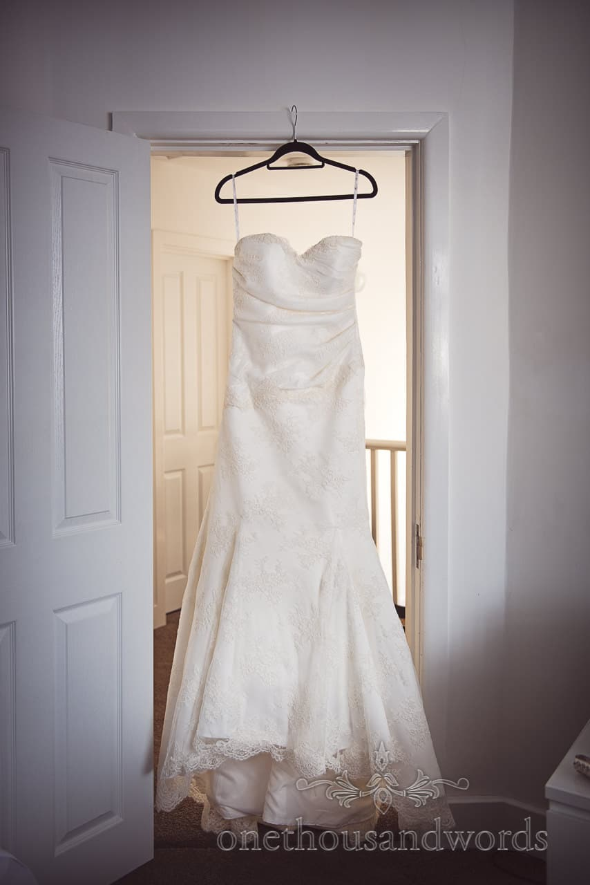 White trumpet skirt strapless wedding dress with lace detail hangs in doorway