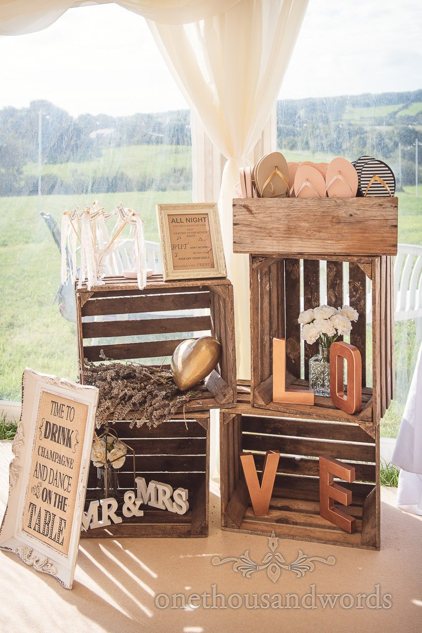Wooden crate wedding decorations with love sign and flip flops and flowers