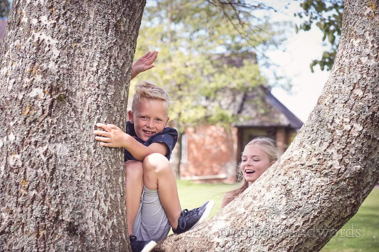 Young guest in tree during drink reception at Coppleridge Inn Wedding