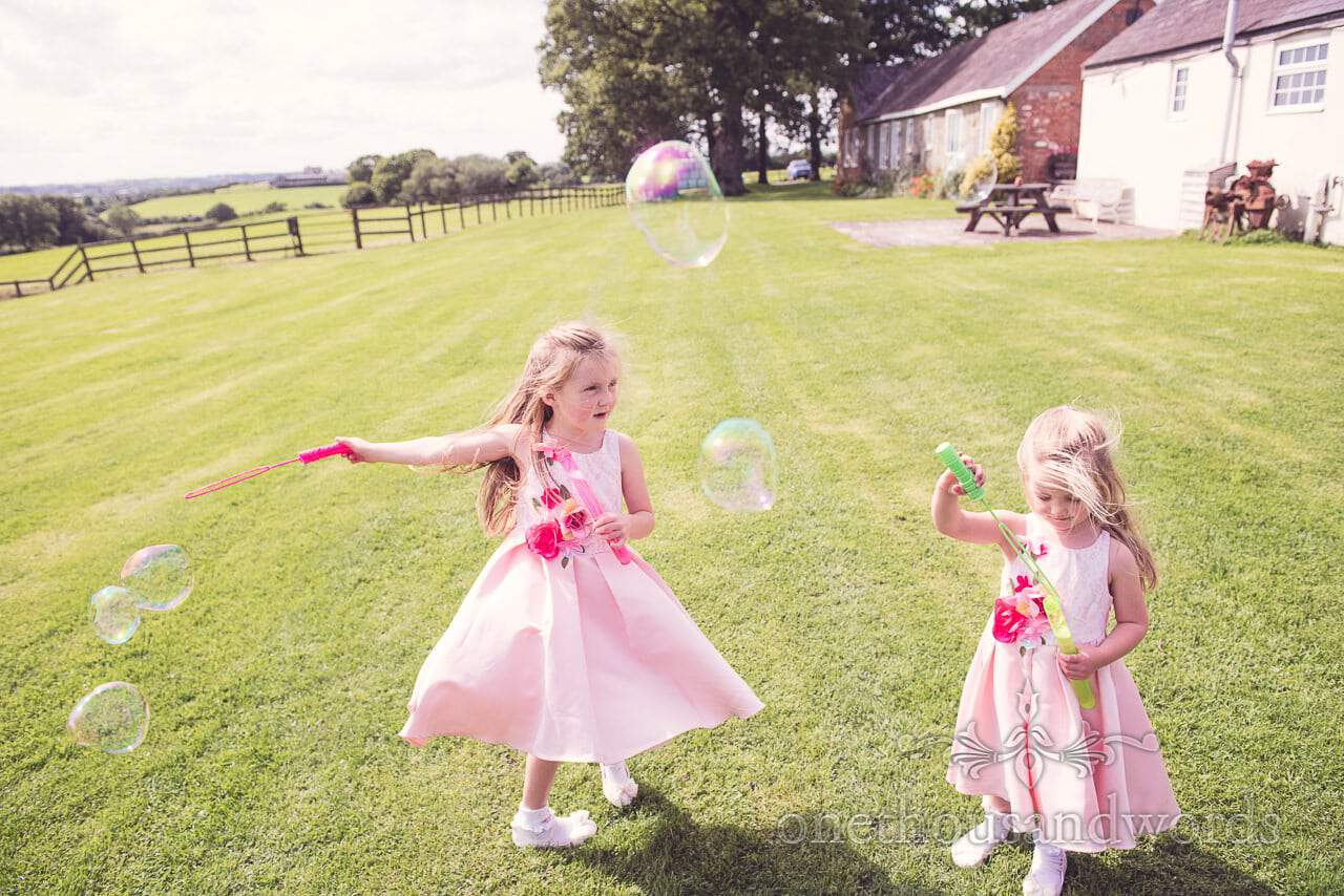 Young wedding guests play with bubbles on lawn at Coppleridge Inn Wedding