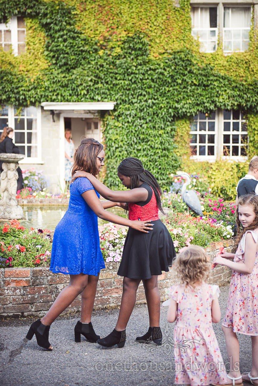 Young wedding guests practice dancing in garden at Coppleridge Inn Wedding Photographs