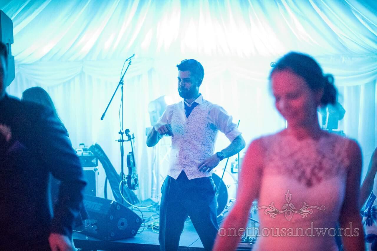Best man dancing under blue disco lights at Marquee wedding evening reception