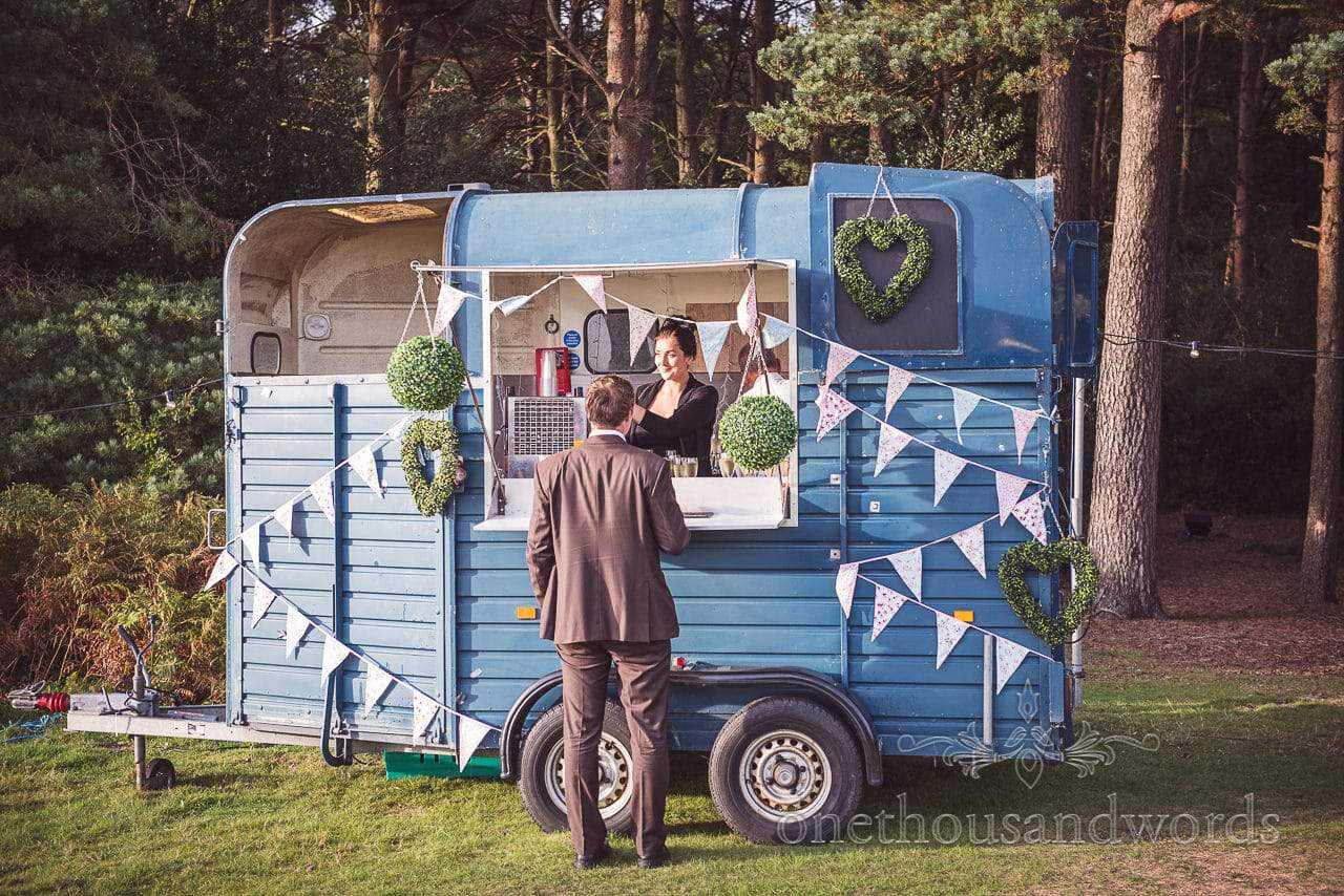 Blue wedding horse box bar at countryside wedding with bunting and topiary