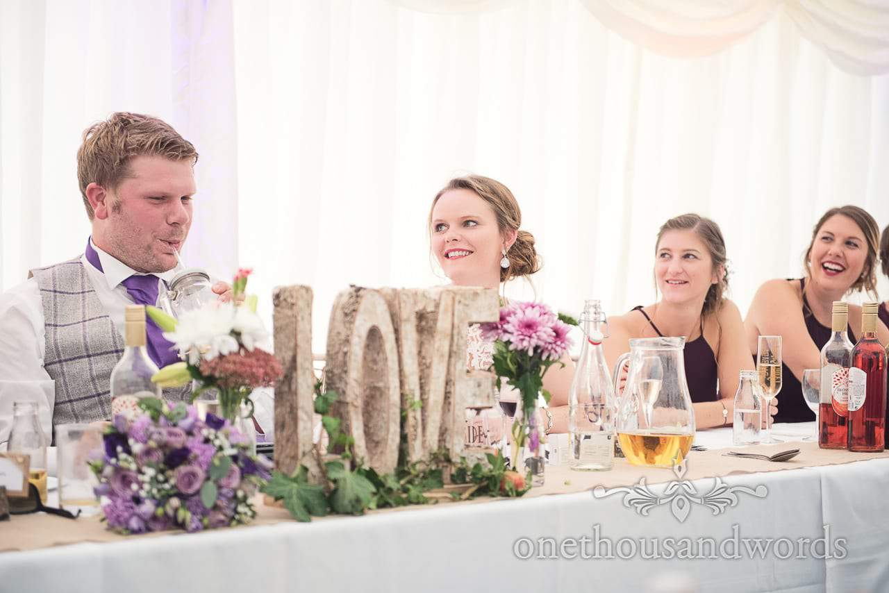 Bride and bridesmaids laugh at wedding speeches in front of wooden love sign
