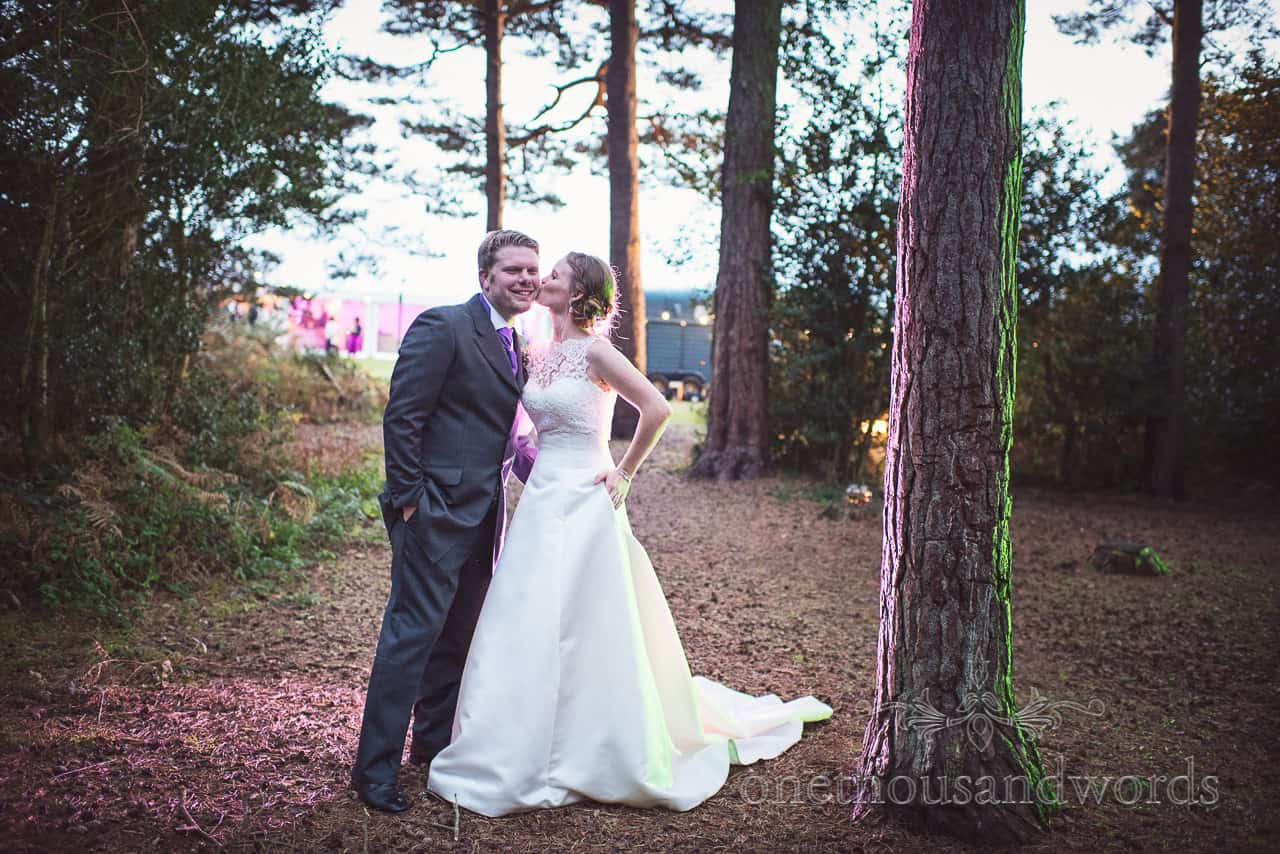 Bride and groom kiss in woodland with lit trees at Dorset countryside wedding