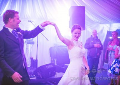 Bride and groom twirl under disco lights during first dance at marquee wedding