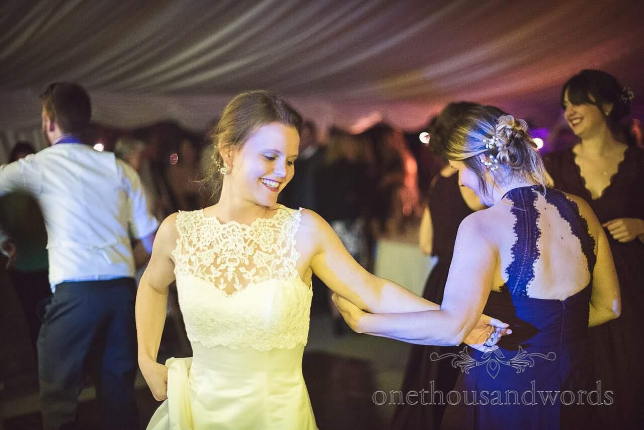 Bride dances with bridesmaids in wedding marquee disco
