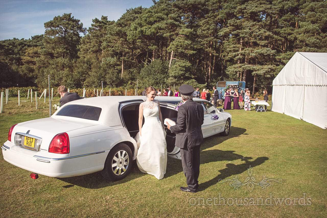Bride exits stretched limousine at countryside marquee wedding in Dorset