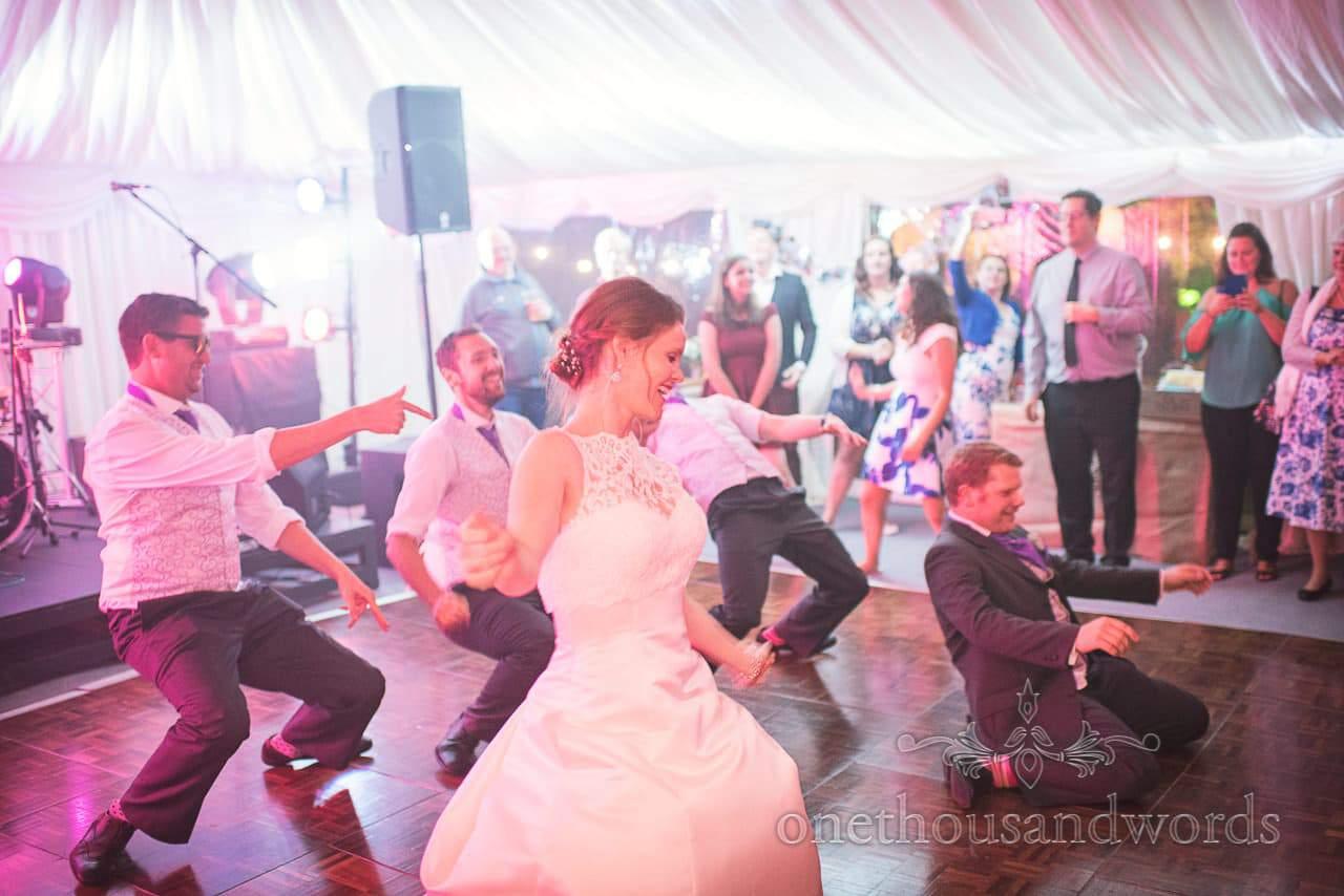 Bride groom and groomsmen dance routine on marquee wedding dance floor