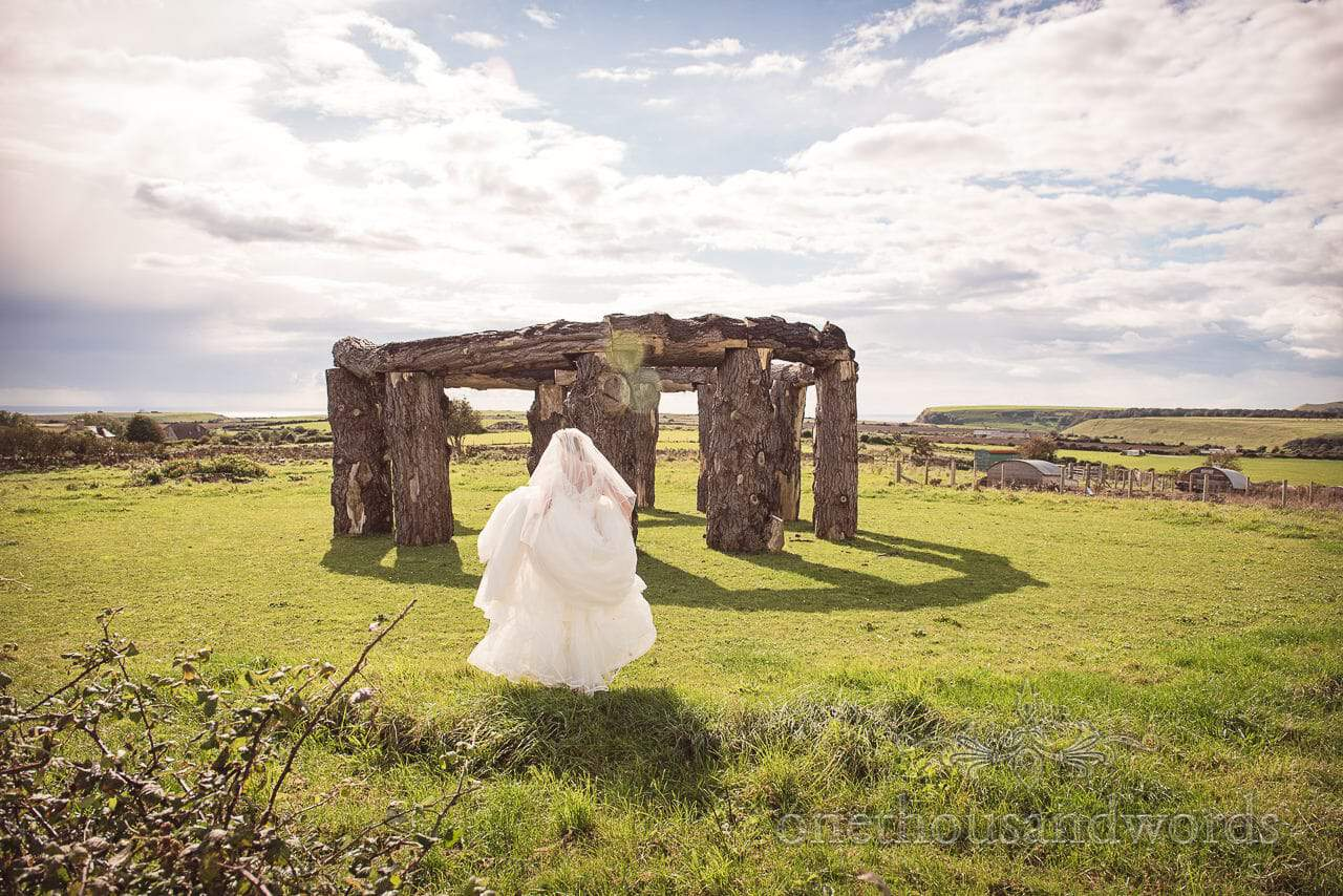 Bride in white wedding dress walks to wood henge in Dorset countryside