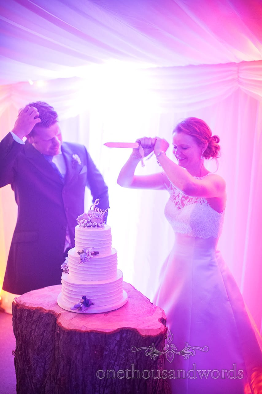 Bride stabs the wedding cake under coloured disco lights at marquee wedding