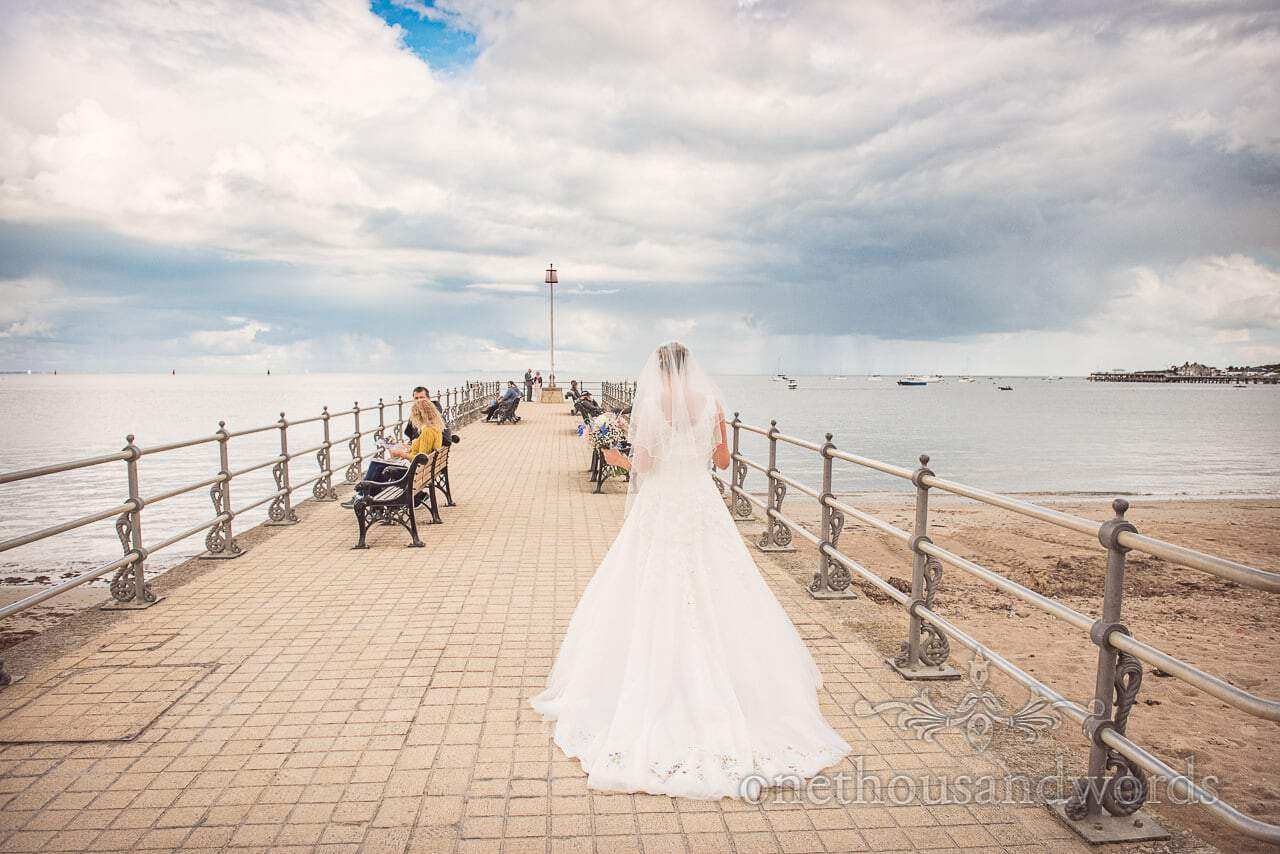 Bride walks onto Swanage Stone pier overlooking the sea with epic rain clouds