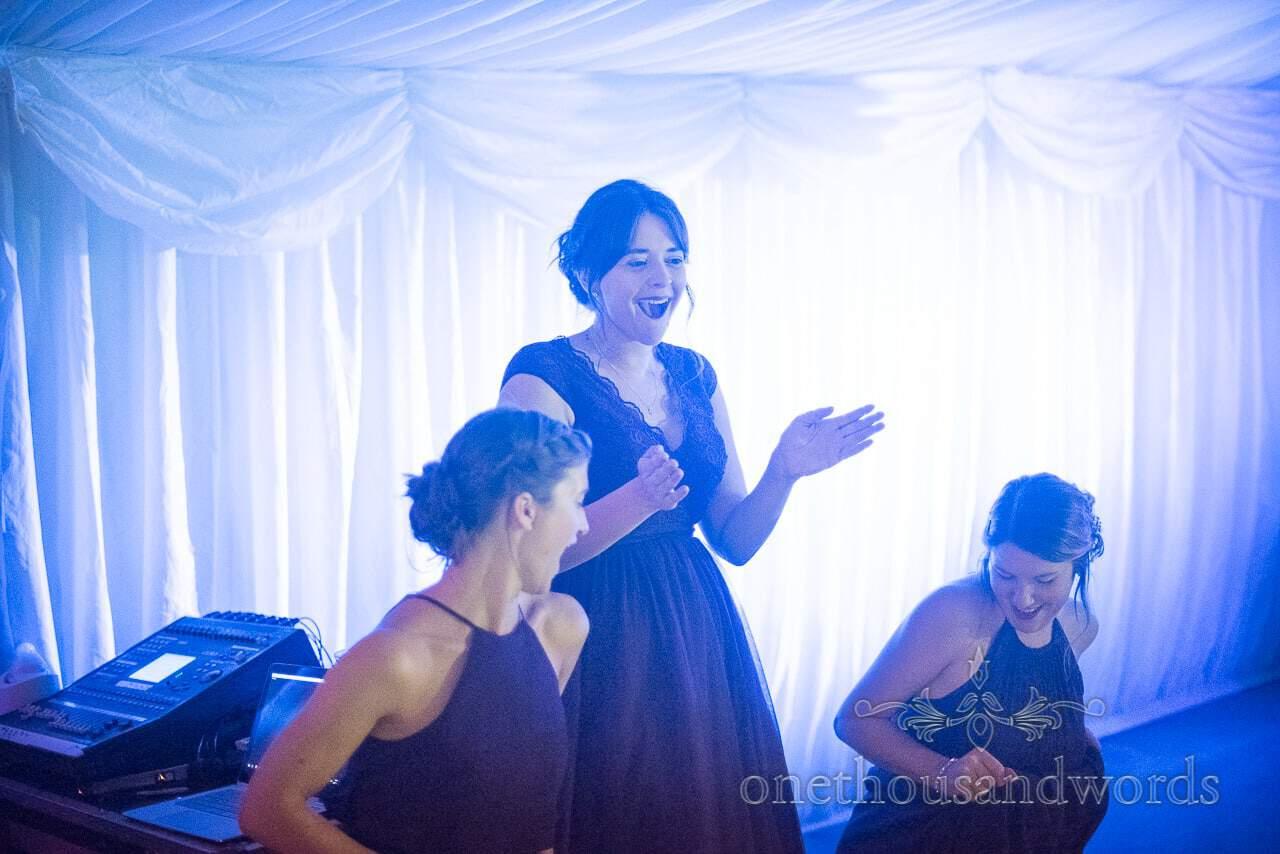 Bridesmaids dance under blue disco lighting at marquee wedding evening reception