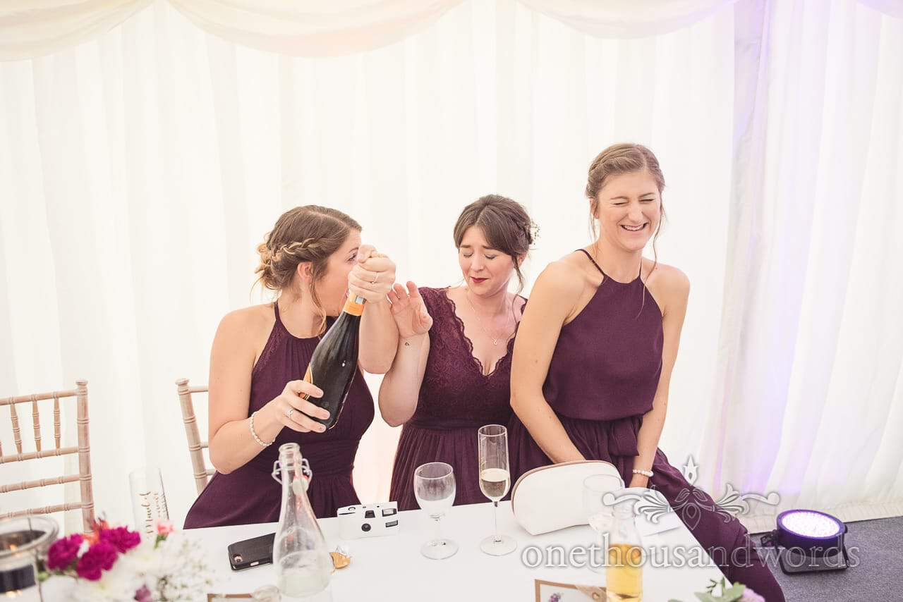 Bridesmaids in purple bridesmaids dresses open champagne bottle in wedding marquee