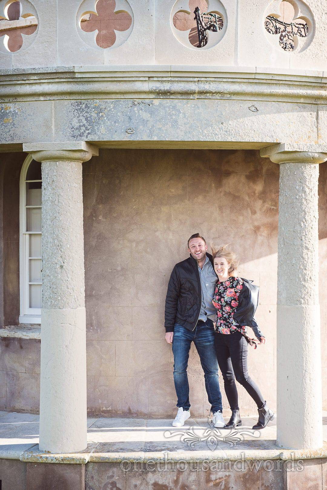 Couple between two columns at cliff top top tower from Kimmeridge Bay Engagement Photographs