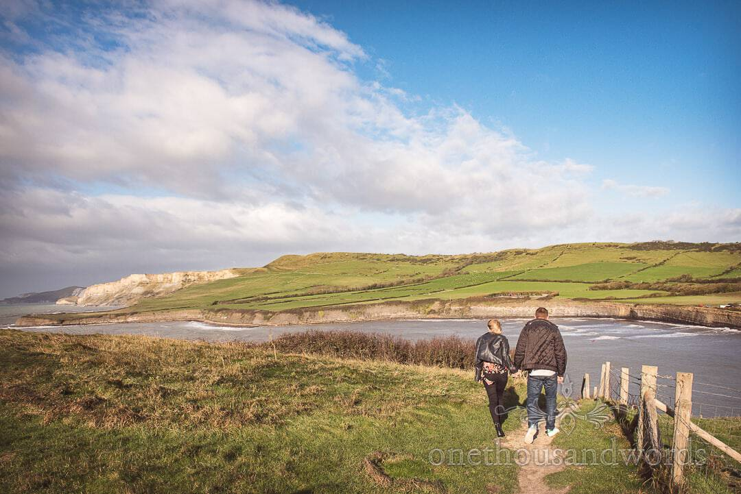 Couple brave hill top wind at Kimmeridge Bay Engagement Photographs