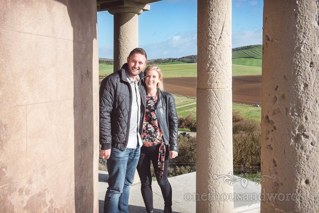 Couple shelter from wind at cliff top tower at Kimmeridge Bay Engagement Photographs