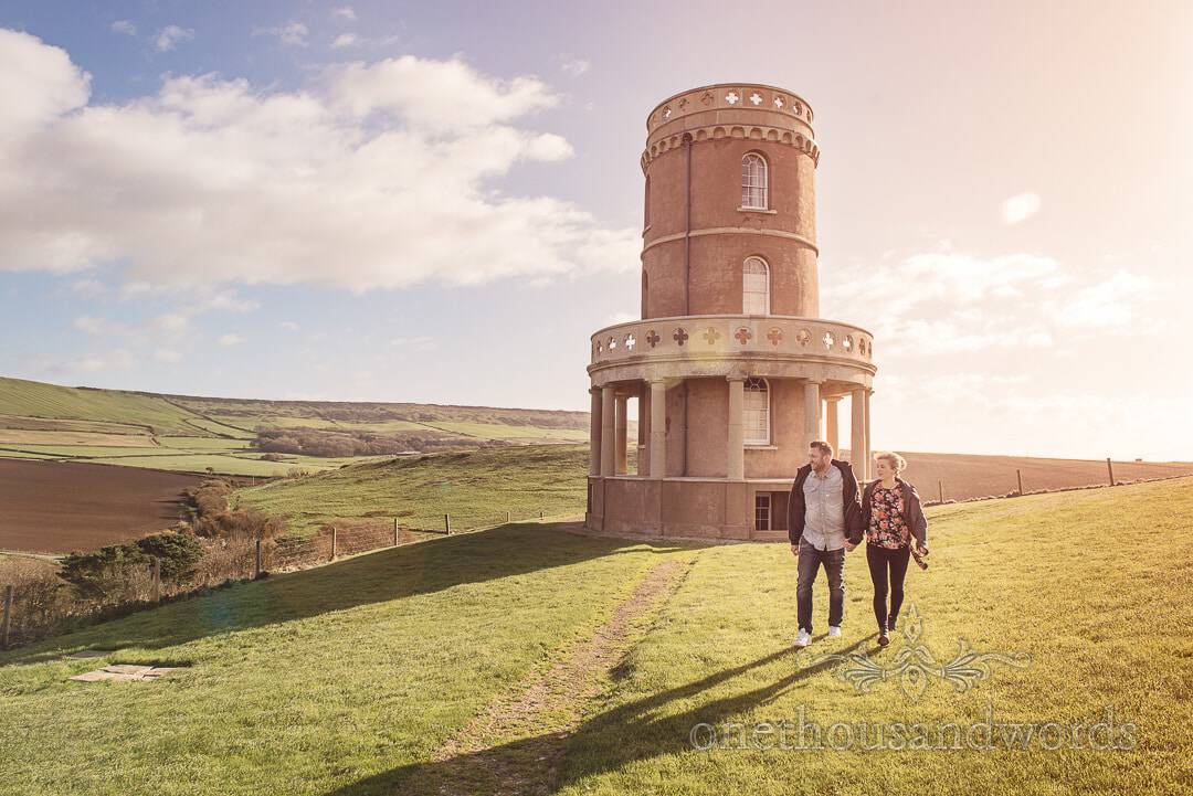 Couple walking away from cliff top tower at Kimmeridge Bay Engagement Photographs