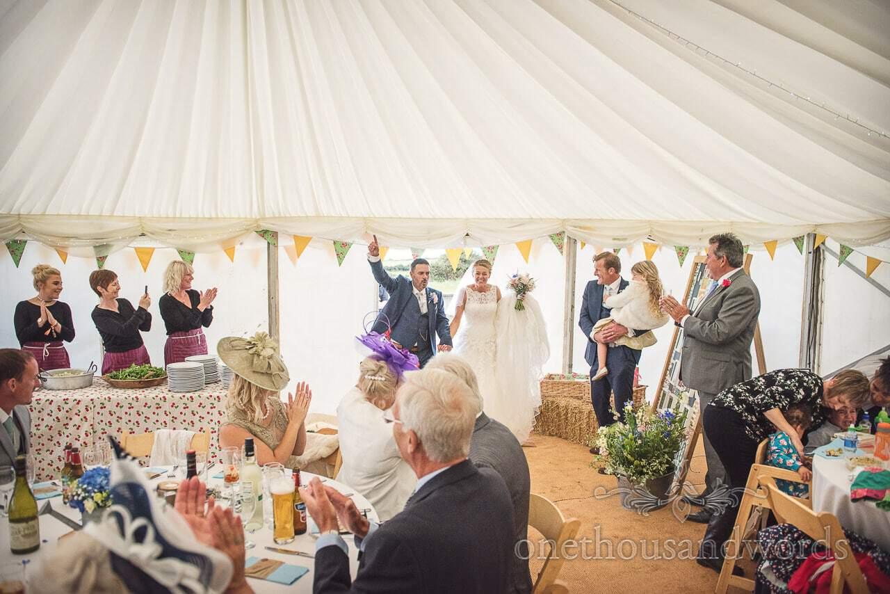 Dorset Wedding Photographer and bride enter wedding breakfast marquee to applause