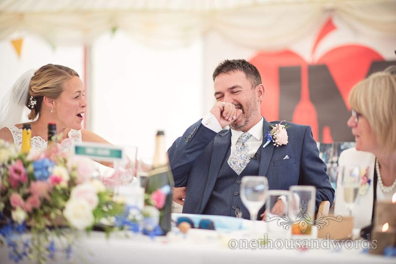 Dorset Wedding Photographer groom and bride react to best man's speech
