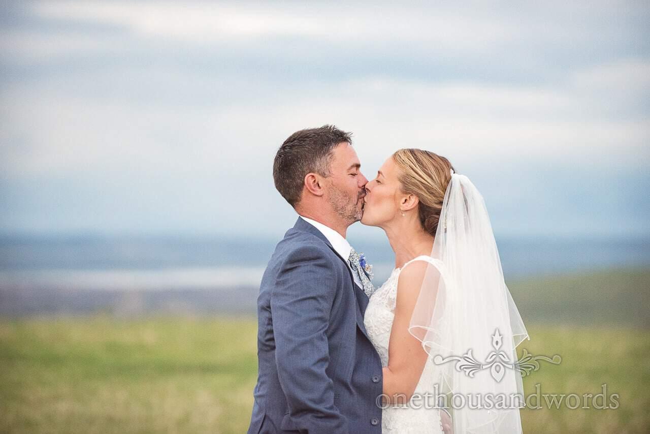 Dorset Wedding Photographer kisses his bride in Dorset countryside