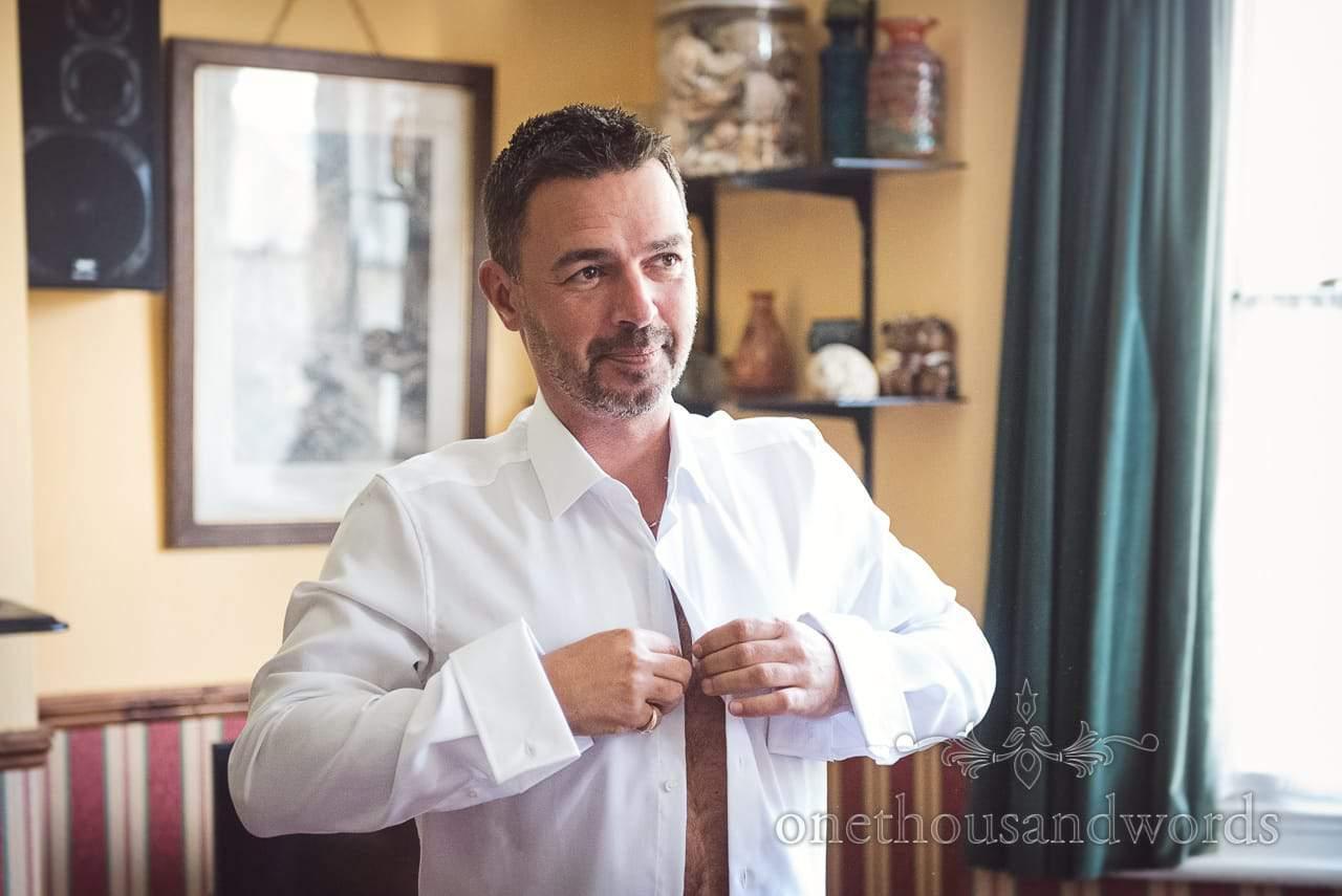 Dorset Wedding Photographer looks contemplative as he buttons shirt on wedding morning