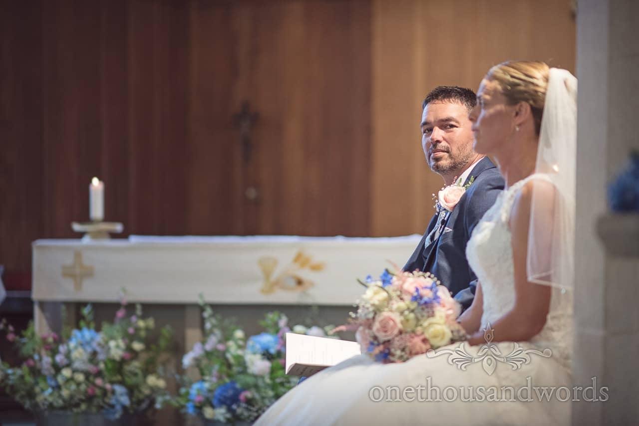 Dorset Wedding Photographer looks into camera during church wedding ceremony
