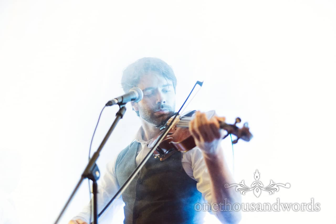 Electric Eden wedding band singer and fiddle player enveloped in smoke at wedding