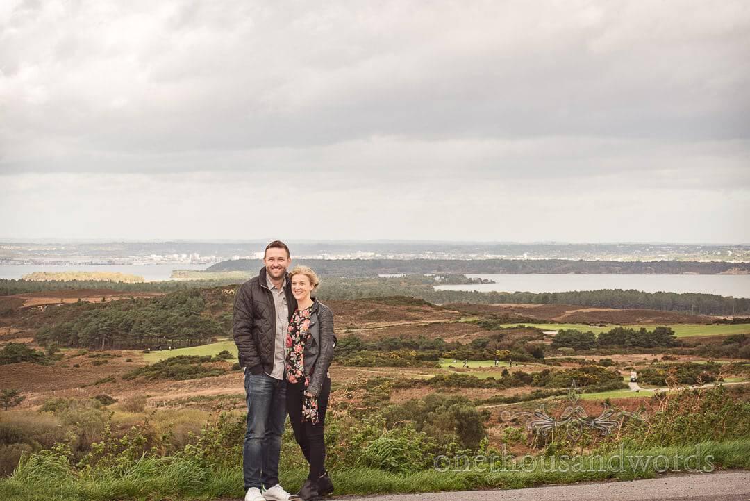 Embracing couple against backdrop of Poole harbour Engagement Photographs