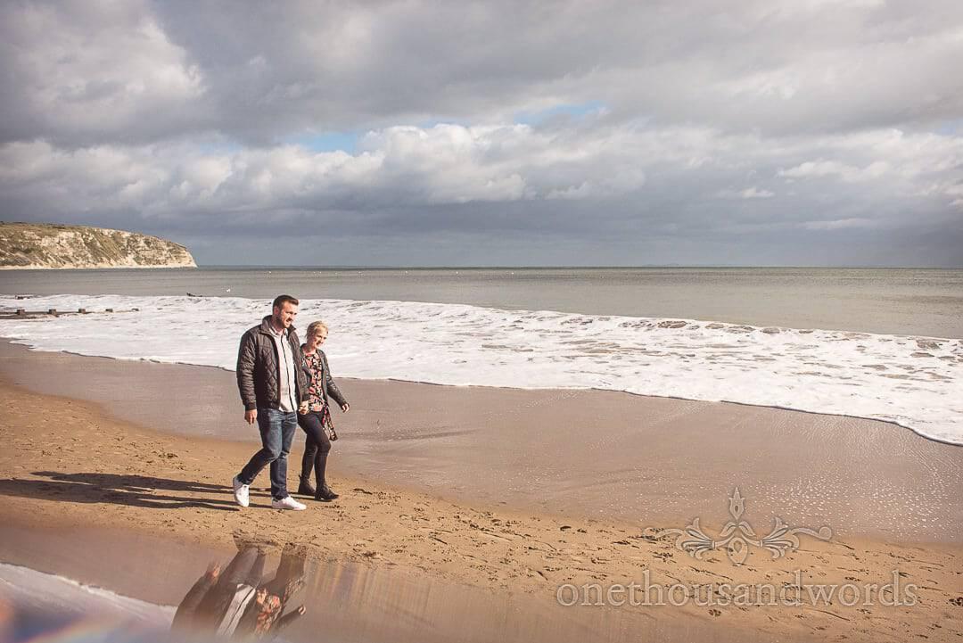 Engaged couple walking in sunshine on Swanage beach