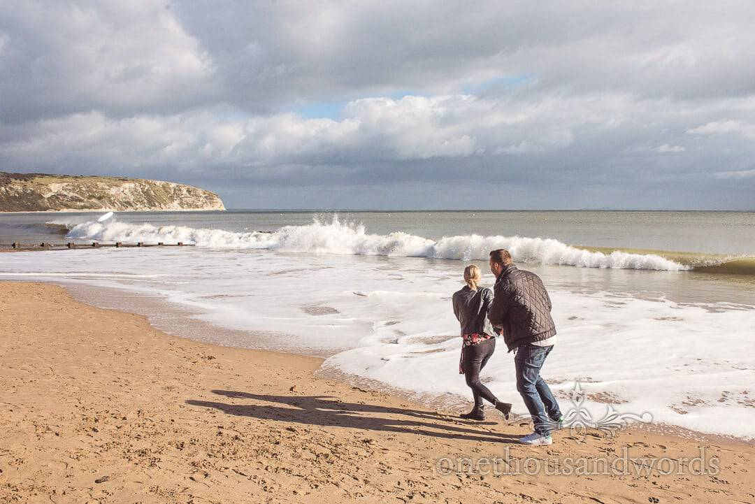 Engagement couple try to keep their feet dry on Swanage beach