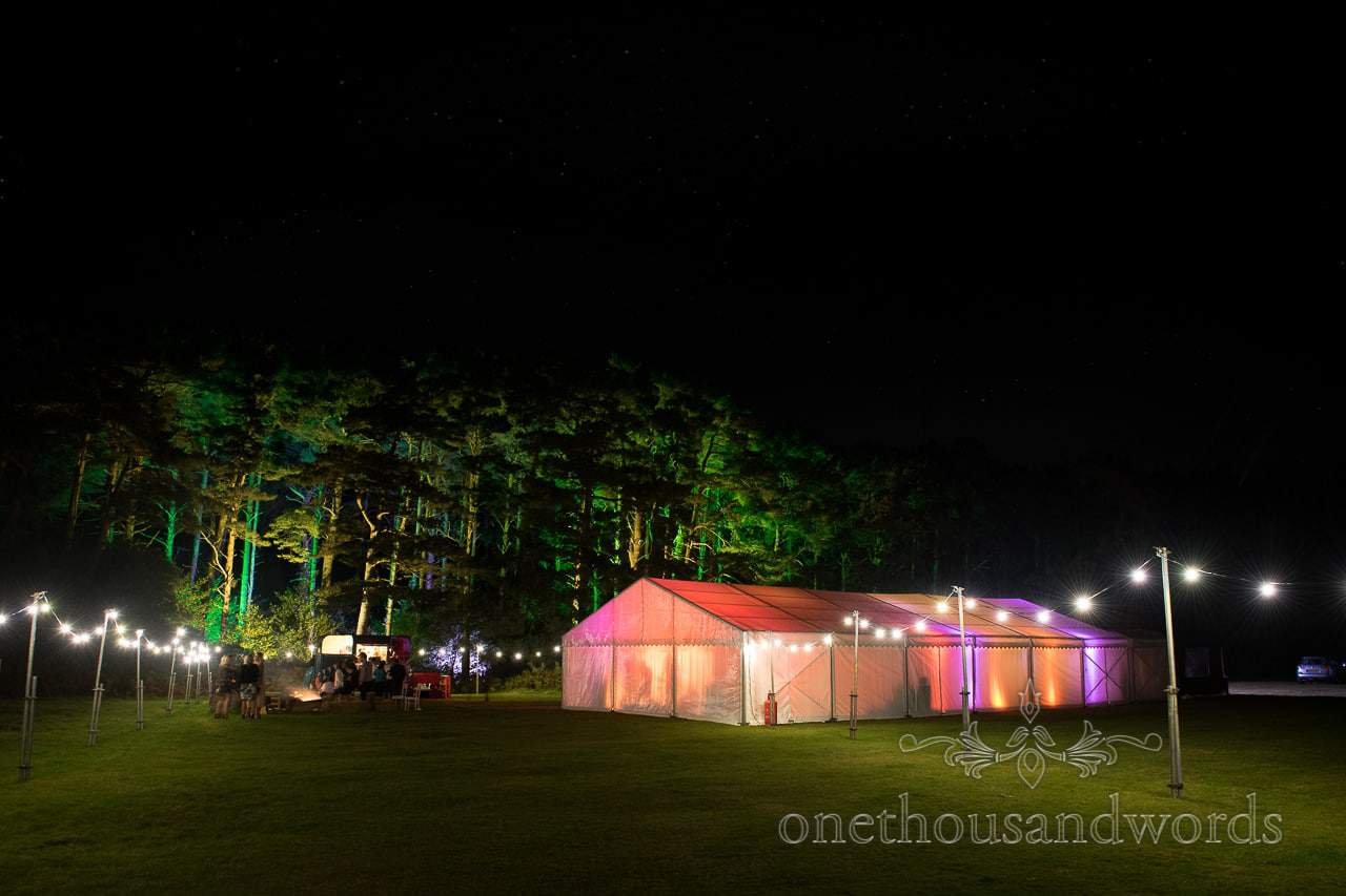Glowing wedding marquee with festoon lighting and glowing trees under stars at night