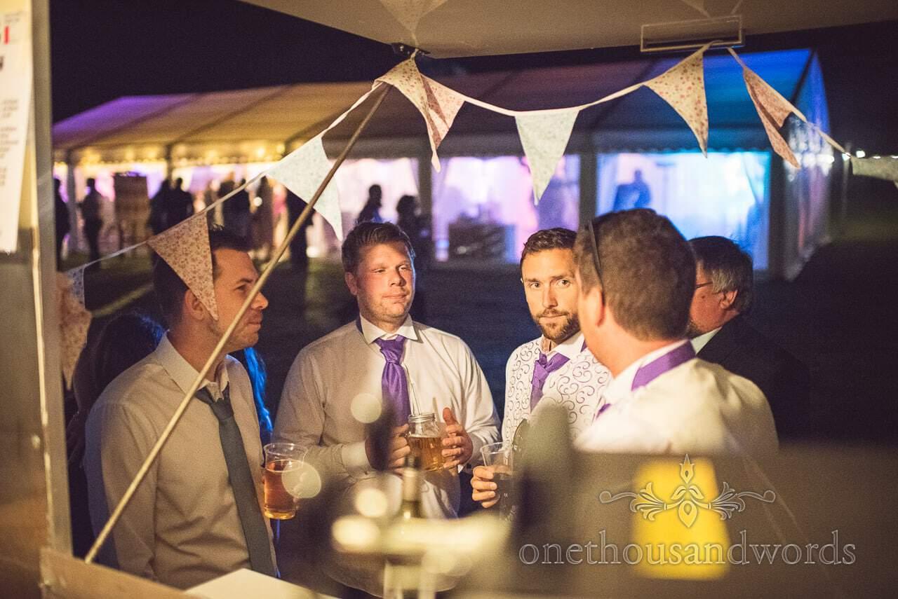 Groom and groomsmen at the horsebox bar at Burnbake wedding reception