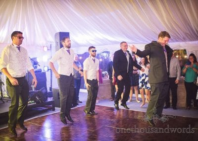 Groom and groomsmen choreographed dance on wedding marquee dance floor