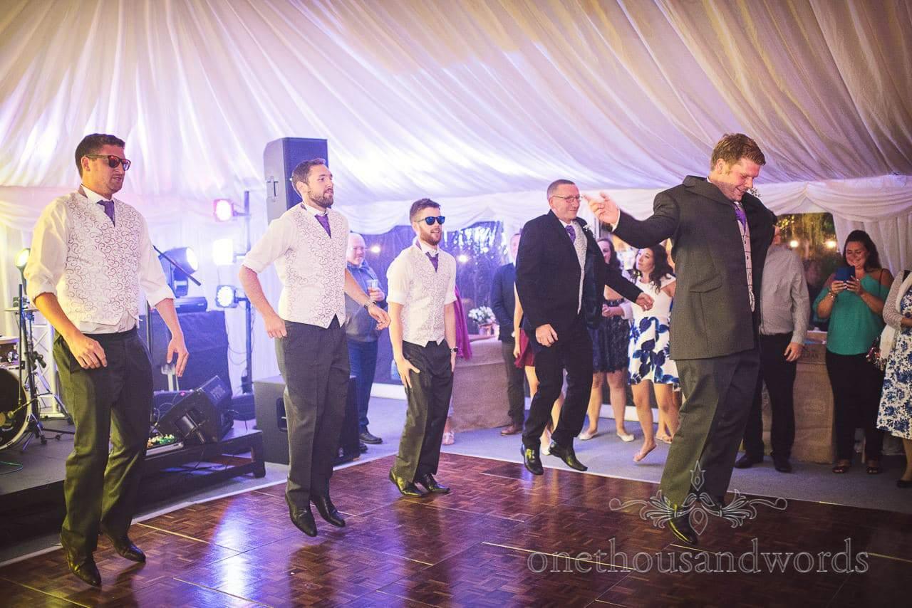 Groom and groomsmen choreographed dance on wedding marquee dance floor