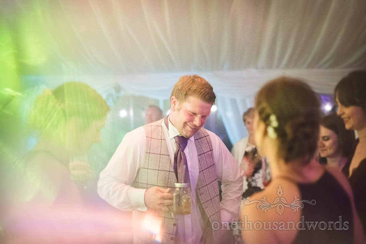 Groom dancing with drink to wedding disco at Swanage Marquee wedding