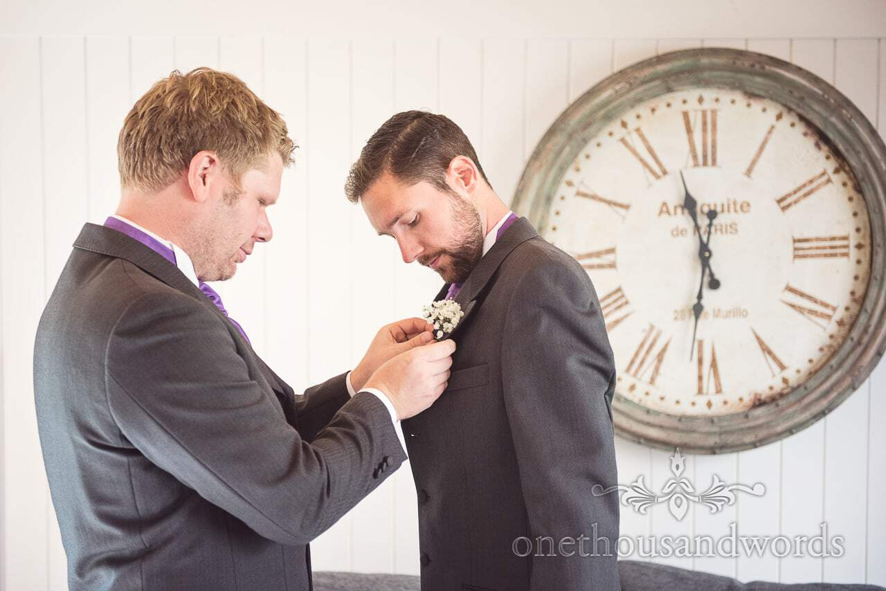 Groom helps groomsmen with buttonhole from Grand Hotel Wedding Photographs